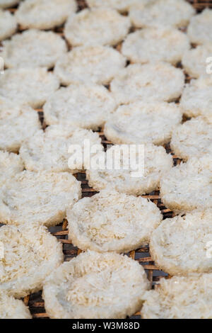 Close-up of sticky rice pressed into round flat cakes drying in the sun on a handmade bamboo tray in Luang Prabang, Laos. - Stock Photo