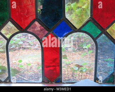 In a stained glass window of geometric shapes, two arches of clear glass show the foliage in the landscape behind - Stock Photo