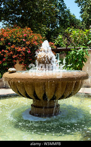 Beautiful, large Spanish-style fountain with falling, splashing water and bougainvillea in the background. Descanso Gardens, La Cañada Flintridge, CA. - Stock Photo