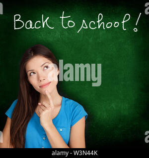 Back to school blackboard - woman student thinking. Female college university student girl thinking Back to School written in on green chalkboard. Multiracial Asian Caucasian student in her 20s. - Stock Photo