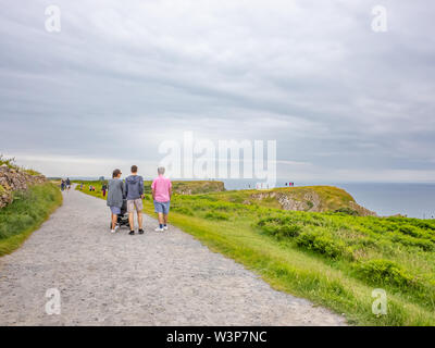 A family group walking along a stretch of the Welsh Coastal path in the village of Rhossili, South Wales - Stock Photo