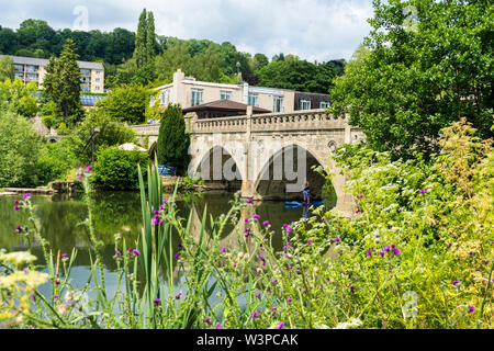 Toll Bridge over River Avon at Bathampton Batheaston border. A woman paddleboarder goes under bridge. - Stock Photo