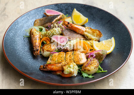 close up of mix grilled seafood and fish platter with fresh salad, prawns, scallop, tuna, salmon, seabass, lemon, green sauce in a black plate profess - Stock Photo