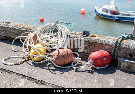 Rope with colourful fishing buoys on the quay of a fishing harbour - Stock Photo