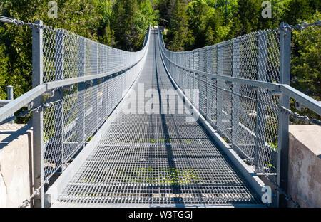 Metal pedestrian suspension bridge over Ranney Gorge in Campbellford, Ontario, Canada. - Stock Photo