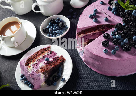 sweet festive cake, blueberry and blackberry sponge cake with cream cheese  inside on a black dish on a concrete table served with a cup of tea, milk - Stock Photo