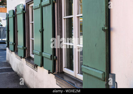 Windows with shutters on the front of the house. - Stock Photo