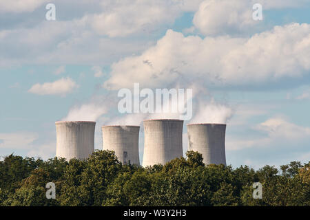 View of smoking chimneys of nuclear power plant, power lines and forest, under blue sky with white clouds - Stock Photo