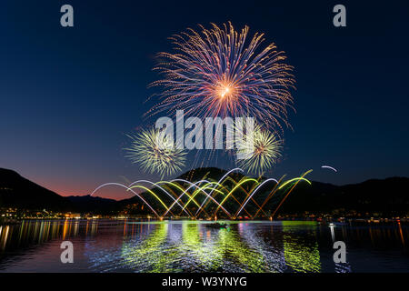 fireworks on the Lugano lake in a beautiful clear summer evening - Stock Photo