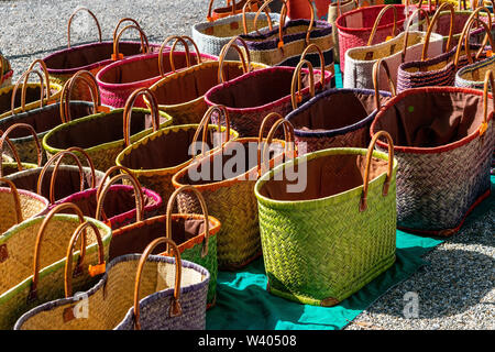 A display of colourful handmade wicker baskets for sale in a French market suitable for carrying shopping - Stock Photo