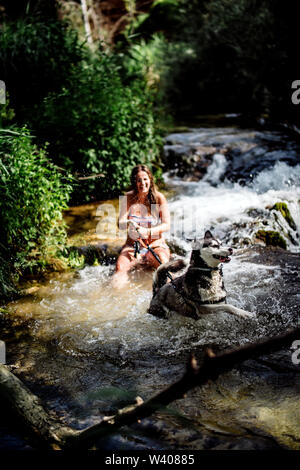 Blond woman bathing in nice river with siberian husky dog. - Stock Photo