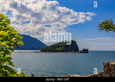 Island of St. Nicholas or Hawaii, small island in the Adriatic sea near Budva Montenegro at sunset - Stock Photo
