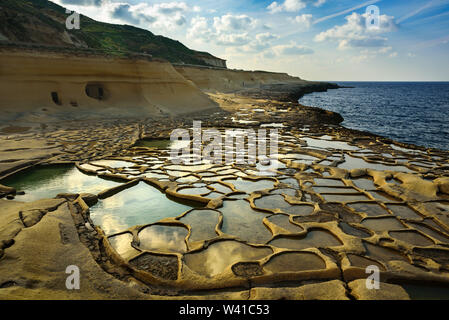 Salt evaporation pans on Malta. Ponds near sea filled with water at sunny day, february 2019 - Stock Photo