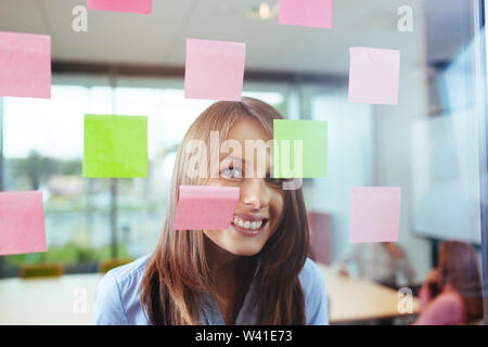 Happy female employee smiling through  window in the office - Stock Photo