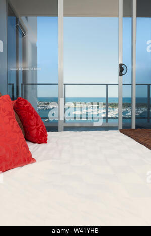 Image of a magazine laying on a bed with red cusions, in a room with a window overlooking an ocean - Stock Photo
