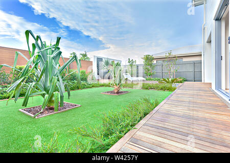 Green garden with fancy trees beside the house facade, the wooden floor with bars next to grass ground with gravel pots, the area covered with wooden - Stock Photo