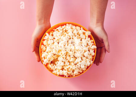 A bowl with popcorn on pink background. Food and entertaiment concept - Stock Photo