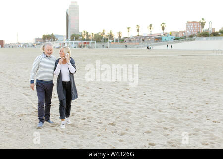 Senior husband walking on sand beach with blonde wife speaking by smartphone. Concept of health way of life and modern technology, pensioners. - Stock Photo