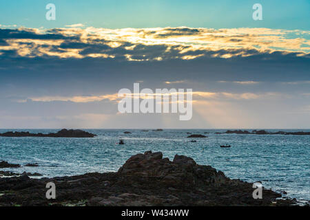 The sun setting over Cobo Bay, Guernsey, Channel Islands UK - Stock Photo