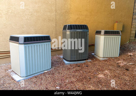 Multiple Air Conditioner Compressors next to large house or building, with room for copy space - Stock Photo