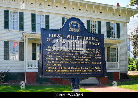 A blue metal sign with gold text in front of the First White House of the Confederacy in Montgomery, AL, USA - Stock Photo