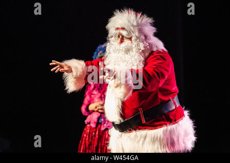 A large man dressed in a Saint Nicholas costume is seen reaching his arms out in front to address youngsters at a christmas festival, against a black background - Stock Photo