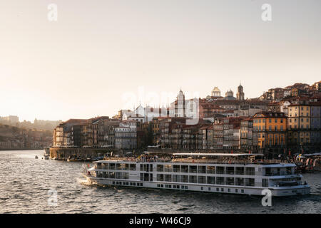 Old town of Porto on Douro River with tourist boats and ferry at sunset, Portugal. - Stock Photo
