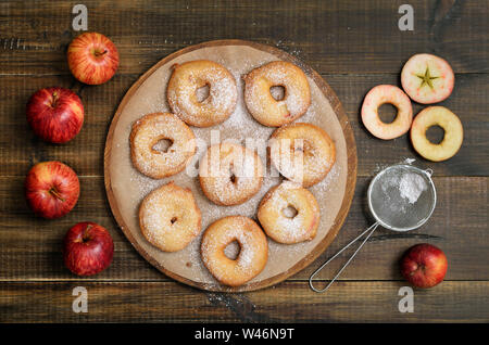 Apple rings and fresh apples on wooden table, top view - Stock Photo