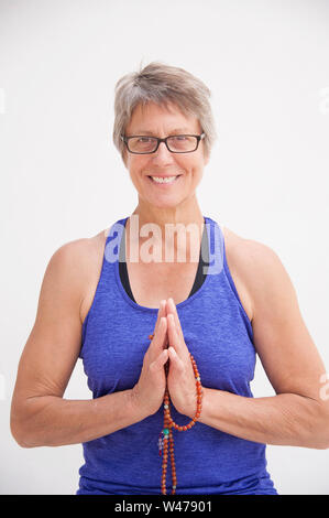 Mature senior woman practing gentle restorative yoga poses photographed in a white background. - Stock Photo