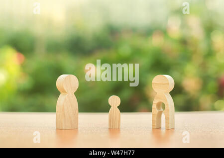 Child's figure stands between father and mother. The child chooses which parent to live with after their divorce. Guardianship over child. Taking into - Stock Photo