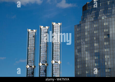 Polycrystalline sillicon photovoltaic solar panel, building in the background - Stock Photo