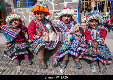 Young girls dressed in traditional Peruvian costume and holding a lamb sit on a step at the market at Pisac (Sacred Valley of the Incas) in Peru. - Stock Photo
