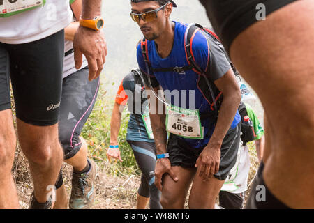 Tired runners in the rain, climbing out of a crater on the steep rough track from les Deux Bras in the Cirque de Mafate during the Grand Raid, Reunion - Stock Photo