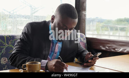 Black guy is making paperwork. Afro american businessman is filling documets in summer tent cafe looking in smartphone. Writing papers. Hot cup of coffee on the table. He wears shirt and suit jacket. - Stock Photo
