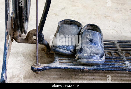 Dust covered shoes resting on the footplate of an old fashioned sewing machine - Stock Photo