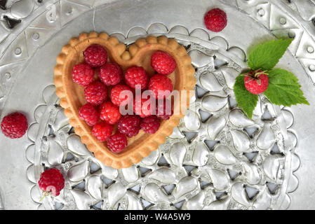 A small cupcake in heart shape with fresh raspberries on a silver-colored cake plate - Stock Photo