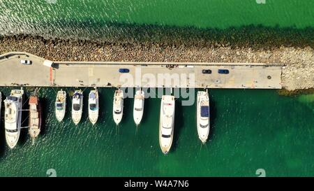 An aerial overhead shot of various types of boats docked near the coast at the sea - Stock Photo