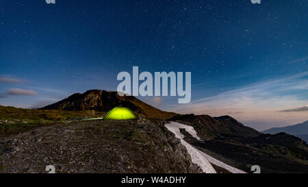 Moonlit scene with illuminated green tent under starry night - fog rolling over mountains - Stock Photo