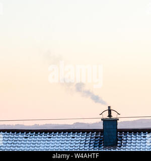 Smoking chimney on a roof during winter in Bavaria, Germany - Stock Photo