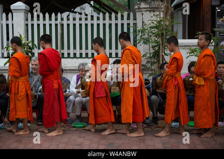 People giving alms to young Buddhist monks on the street early in the morning in Luang Prabang, Laos. The ritual is called Tak Bat. - Stock Photo