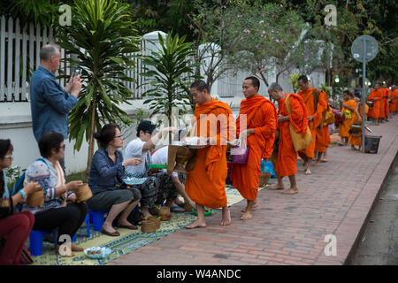 People giving alms to Buddhist monks on the street early in the morning in Luang Prabang, Laos. The ritual is called Tak Bat. - Stock Photo