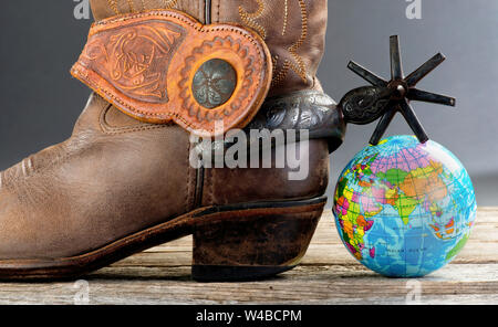 World cowboy with Mexican spurs and small globe. - Stock Photo