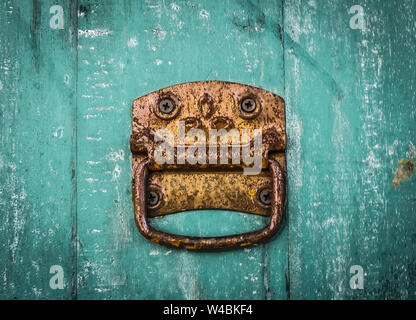 Old rusty knober on the shabby green surface of the door. - Stock Photo