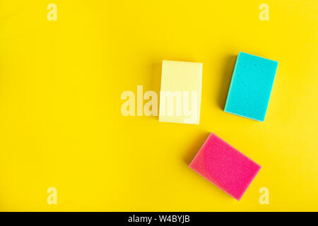 Multi-colored sponges for washing dishes and cleaning on a bright yellow background. space for text - Stock Photo