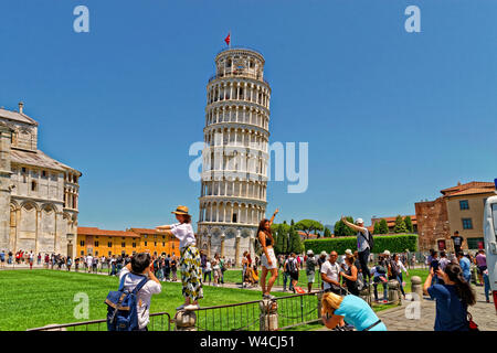 The Leaning Tower of Pisa and Selfie taking tourists at Pisa, Tuscany, Italy. - Stock Photo