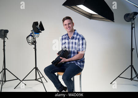 Portrait Of Male Photographer In Studio For Photo Shoot With Camera And Lighting Equipment - Stock Photo
