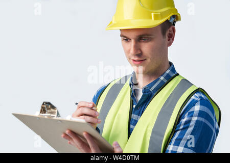 Studio Shot Of Builder Architect With Clipboard Against White Background - Stock Photo