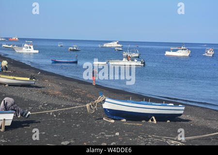 Seascape of natural wonder and UNESCO heritage - stromboli volcanic beach in Italy. Man walking and talking on his phone surrounded by fishing boats - Stock Photo