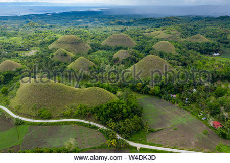 Aerial view of rural farmland and conical limestone karsts in a tropical landscape (Chocolate Hills, Bohol) - Stock Photo