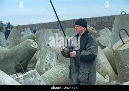 man fisherman on the breakwaters, fisherman with a fishing rod on the sea breakwaters, Baltic sea, Kaliningrad region, Russia, March 21, 2019 - Stock Photo